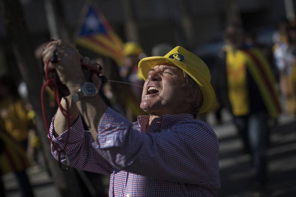 A Catalan pro-independence demonstrator drinks using a wineskin, as they arrive to Madrid, Spain, Saturday, March 16, 2019. Tens of thousands are marc