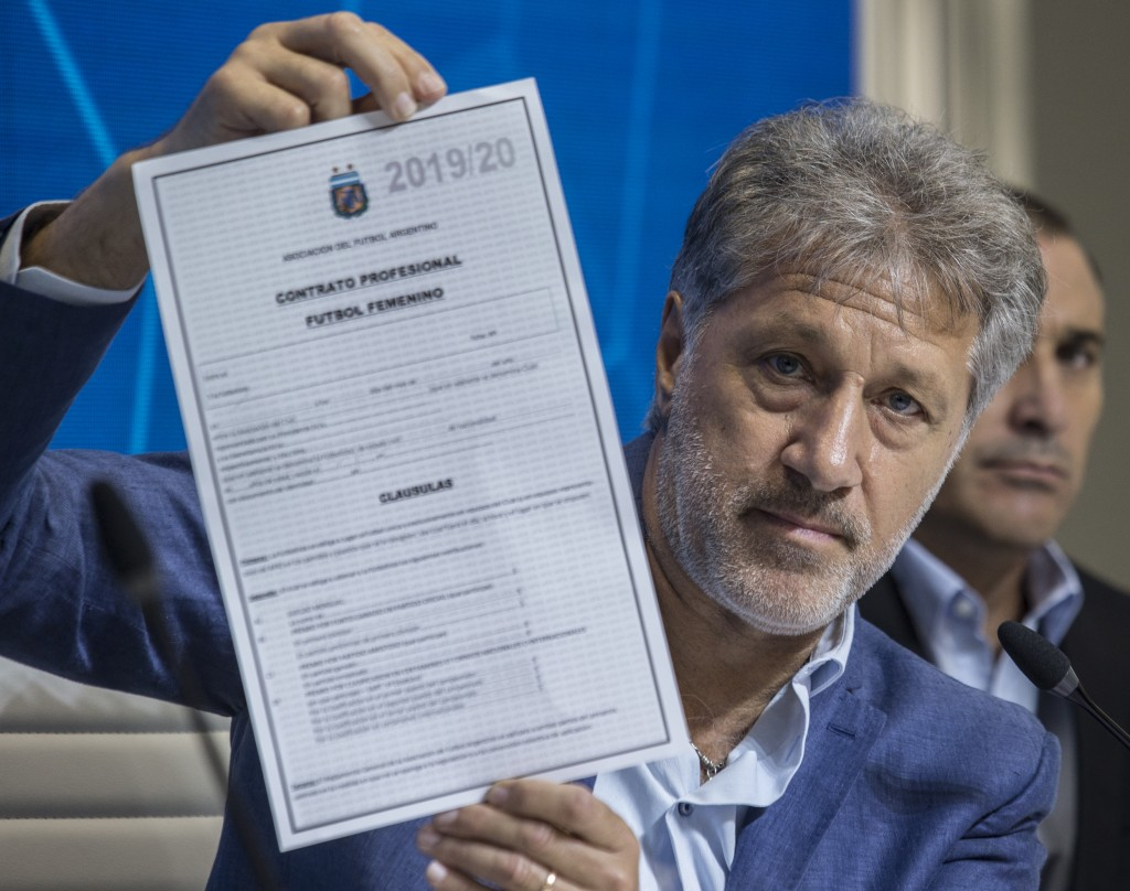 General Secretary of the Argentina's Footballers' Union (FAA) Sergio Marchi holds up the contract to implement a plan to professionalize women's socce