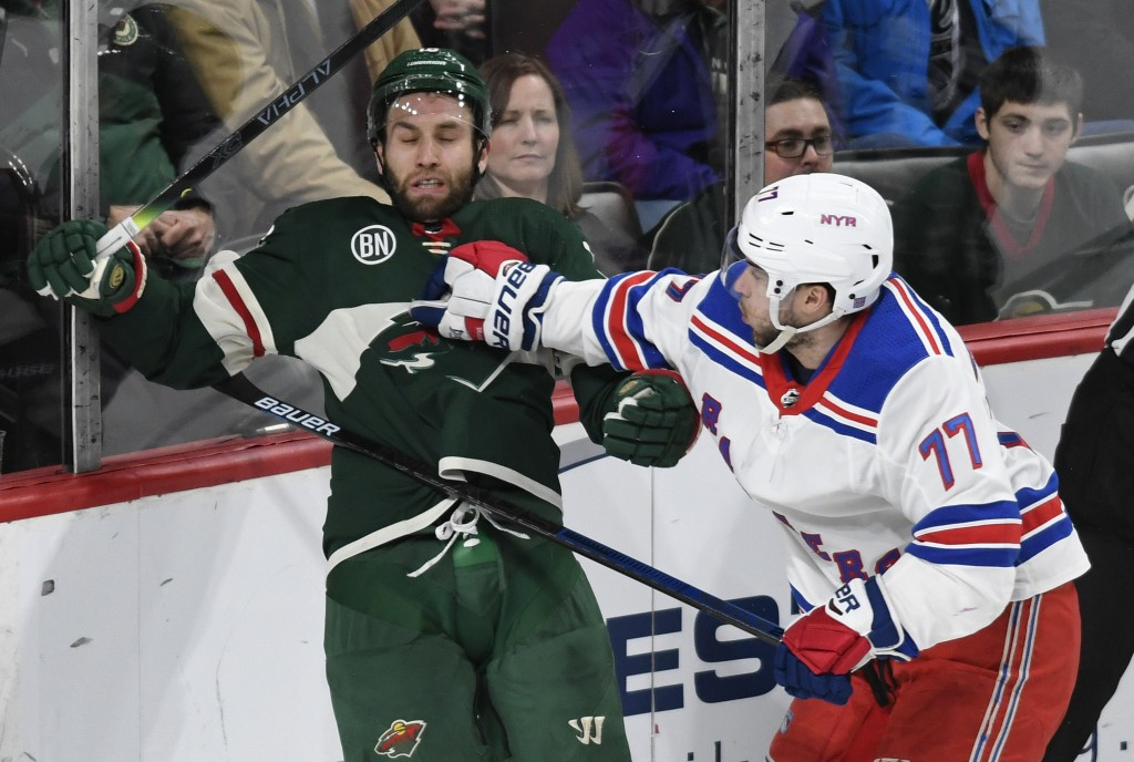 New York Rangers' Tony DeAngelo, right, checks Minnesota Wild's Jason Zucker, left, in the first period of an NHL hockey game Saturday, March 16, 2019...
