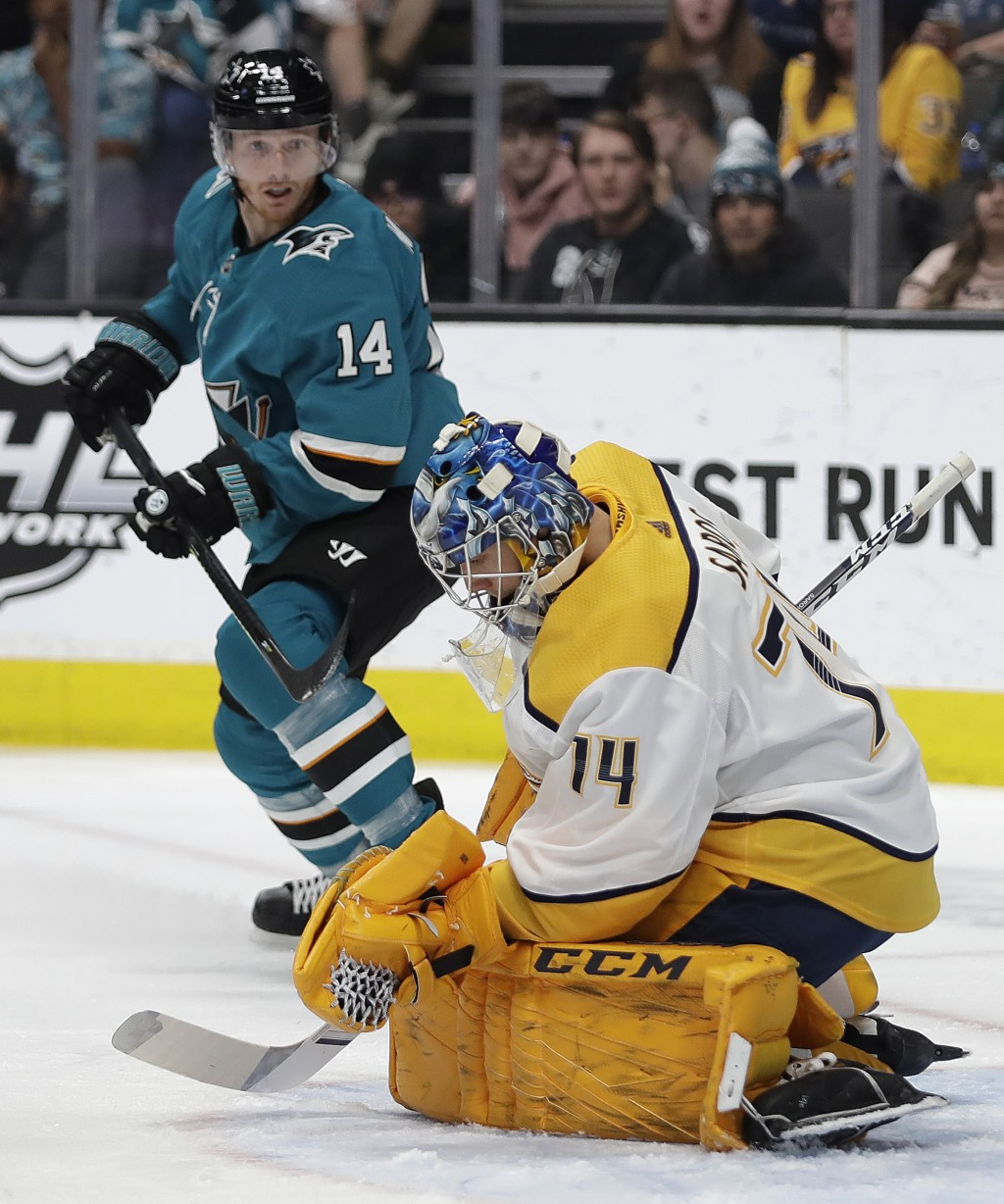 Nashville Predators goalie Mattias Ekholm, right, blocks a shot from San Jose Sharks' Gustav Nyquist during the first period of an NHL hockey game Sat