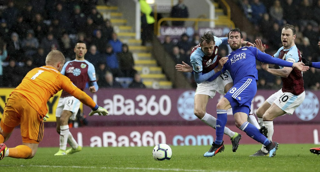 Burnley's Peter Crouch, third right, and Leicester City's Christian Fuchs, second right, battle for the ball as Leicester City goalkeeper Kasper Schme