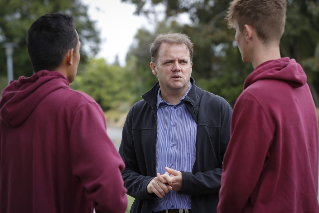 Cashmere High School principal Mark Wilson, center, speaks with his students at the school in Christchurch, New Zealand, Sunday, March 17, 2019. Three