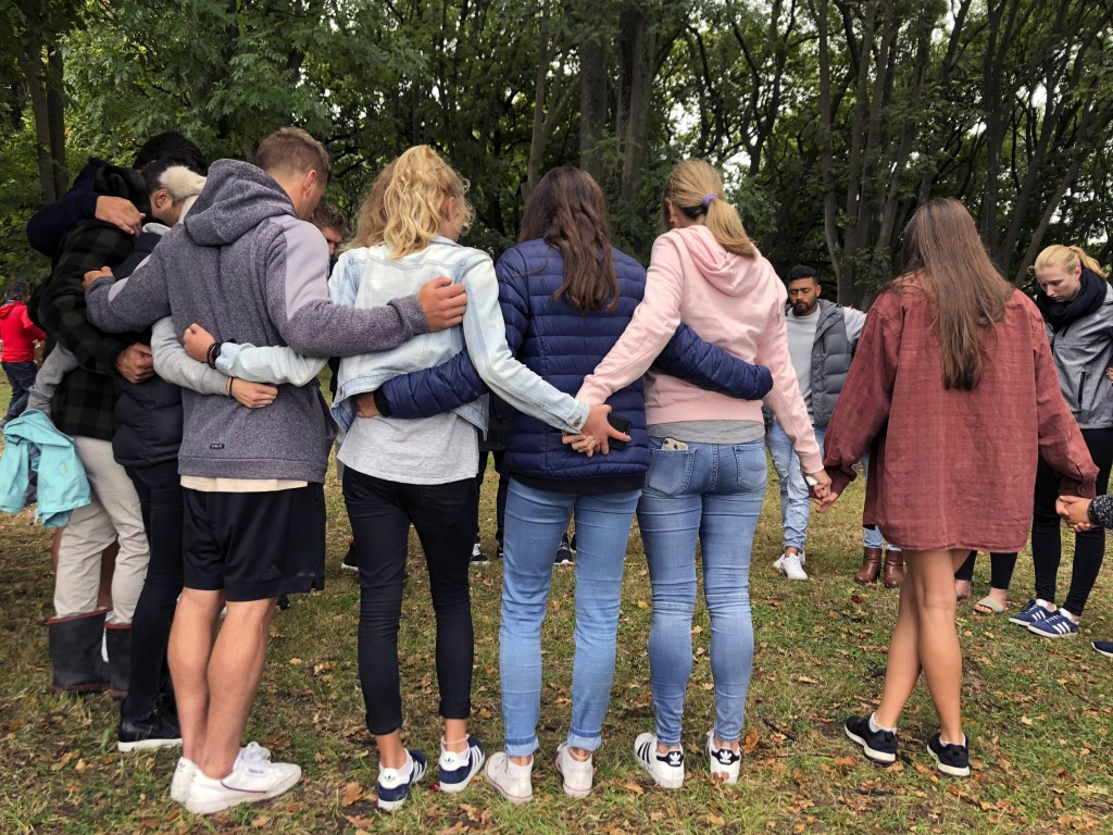 Mourners link arms in Hagley Park near the Al Noor mosque, one of the mosque shooting sites in Christchurch, New Zealand, Sunday, March  17, 2019. An