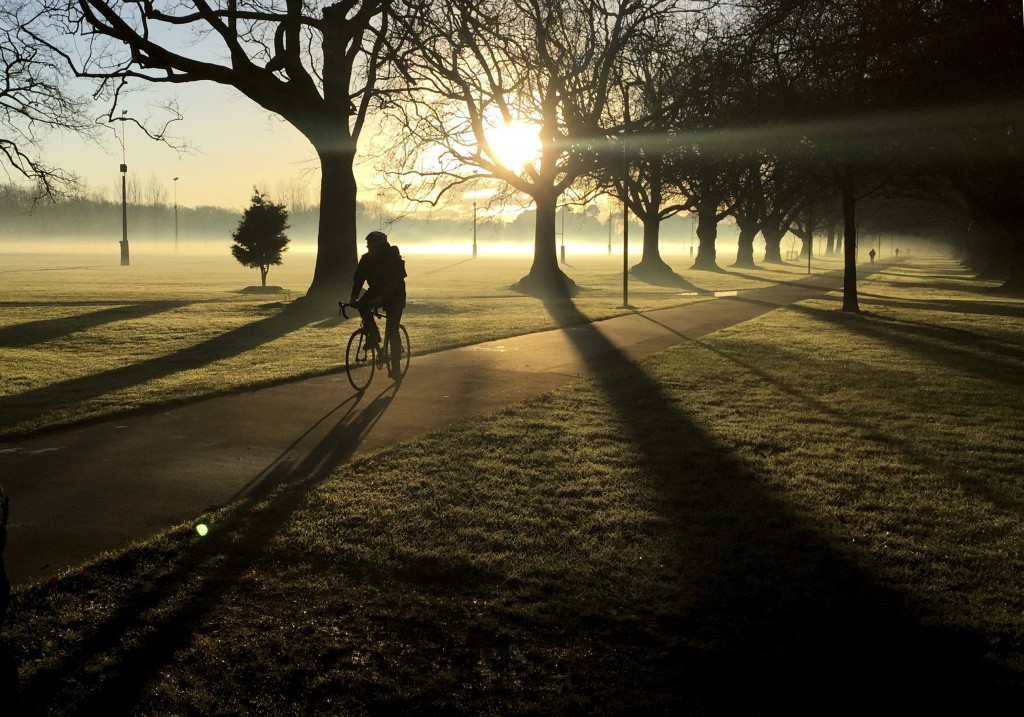 FILE - In this June, 26, 2017, file photo, a cyclist makes his way through a mist covered Hagley Park in central Christchurch, New Zealand. Despite it