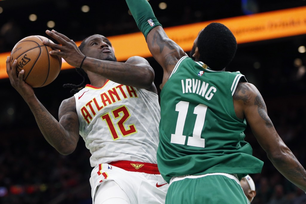 Atlanta Hawks' Taurean Prince (12) shoots against Boston Celtics' Kyrie Irving (11) during the second half of an NBA basketball game in Boston, Saturd
