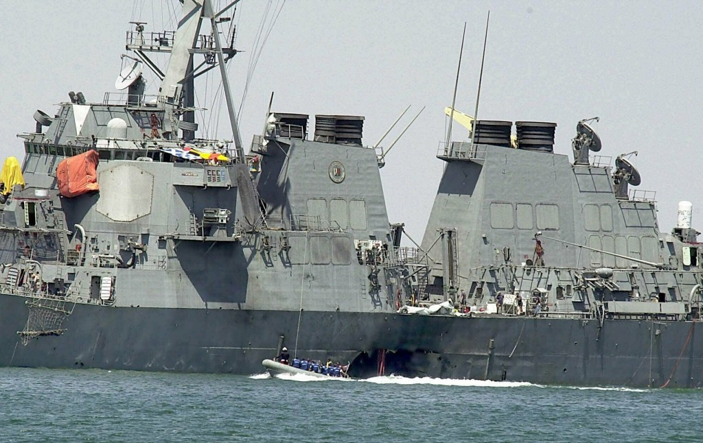 FILE - In this Oct. 15, 2000 file photo, experts in a speed boat examine the damaged hull of the USS Cole at the Yemeni port of Aden after an al-Qaida