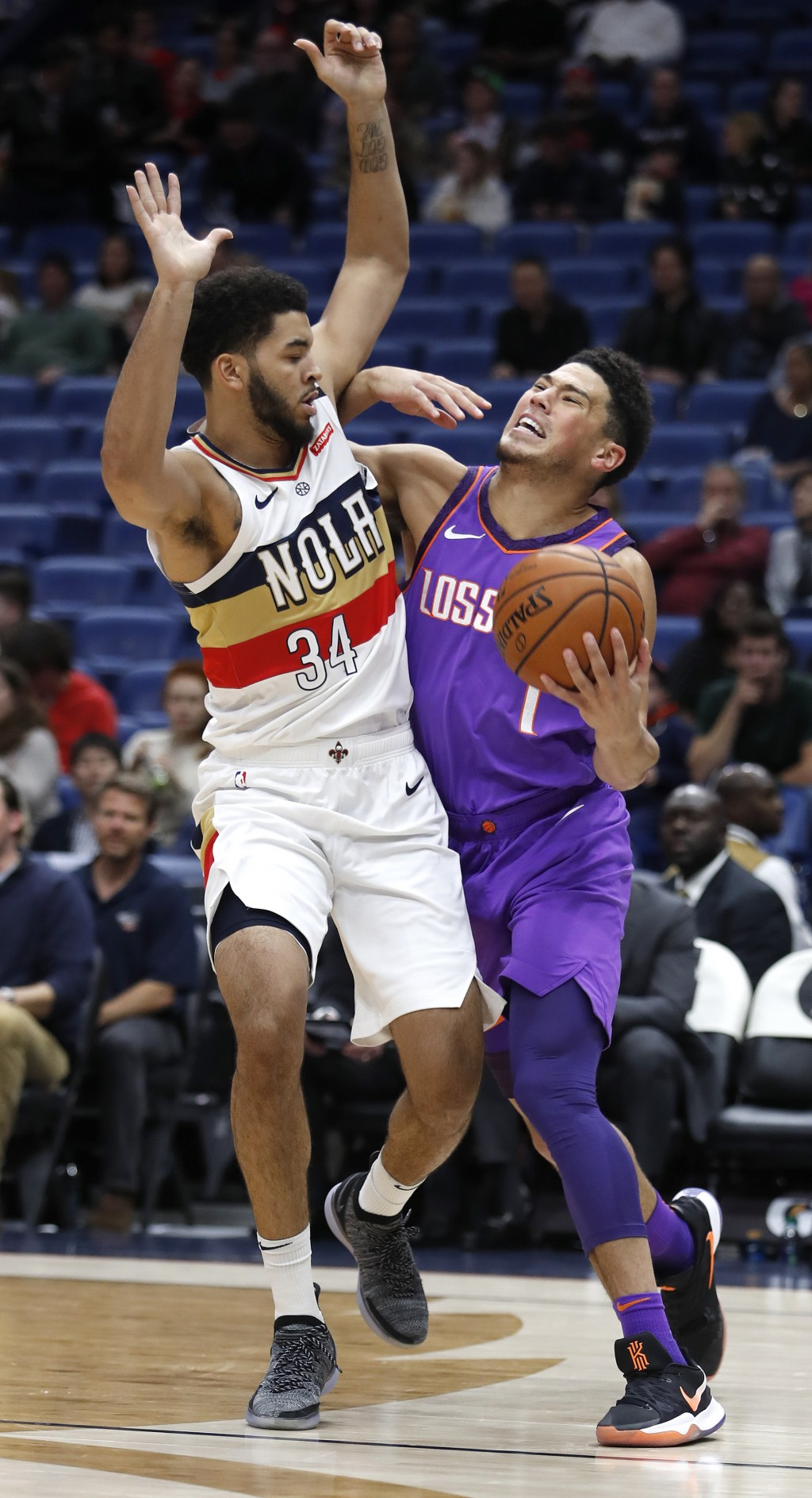 Phoenix Suns guard Devin Booker (1) is defended by New Orleans Pelicans guard Kenrich Williams (34) during the first half of an NBA basketball game in