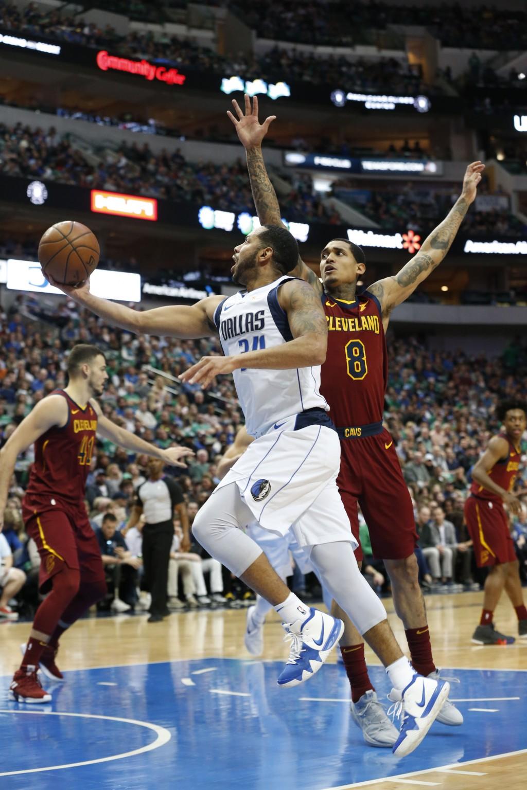 Dallas Mavericks guard Devin Harris (34) makes a layup next to Cleveland Cavaliers guard Jordan Clarkson (8) during the first half of an NBA basketbal