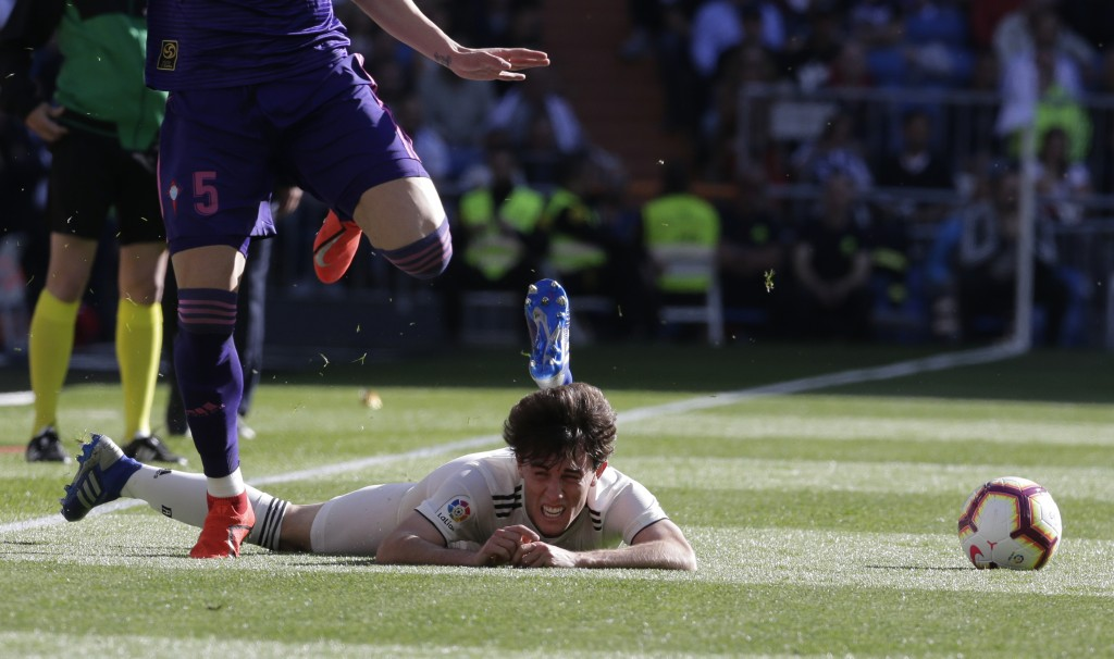 Real Madrid's Alvaro Odriozola, right, is tackled by Celta's Okay Yokuslu during a Spanish La Liga soccer match between Real Madrid and Celta at the S