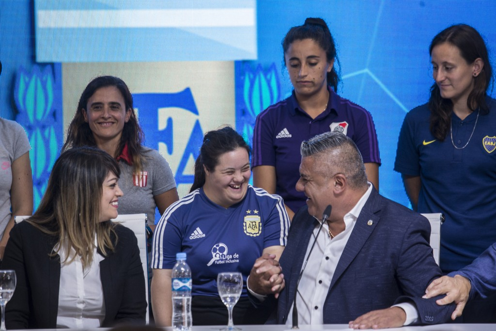 Claudio Tapia, president of Argentina's Soccer Federation, greets a soccer player during a press conference to announce the early implementation of a