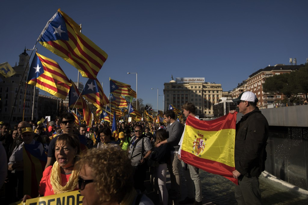 "Protesters hold a Spanish flag as Catalan pro-independence demonstrators wave ""esteladas,"" or separatist flags as they arrive to Madrid, Spain, Saturd"