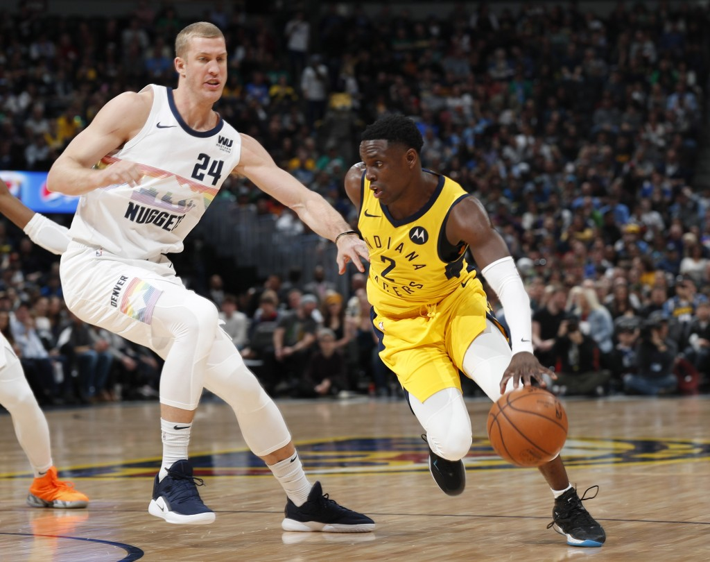 Indiana Pacers guard Darren Collison, right, drives the lane past Denver Nuggets forward Mason Plumlee during the first half of an NBA basketball game