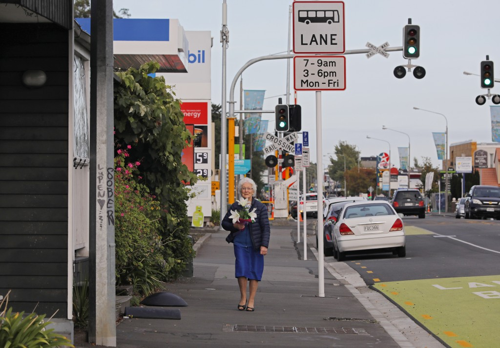 A woman holds flowers on her way towards the Masjid Al Noor mosque to pay her respects in Christchurch, New Zealand, Sunday, March 17, 2019, where one
