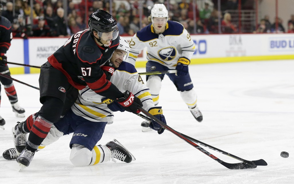 Carolina Hurricanes' Trevor van Riemsdyk (57) and Buffalo Sabres' Conor Sheary chase the puck during the second period of an NHL hockey game in Raleig