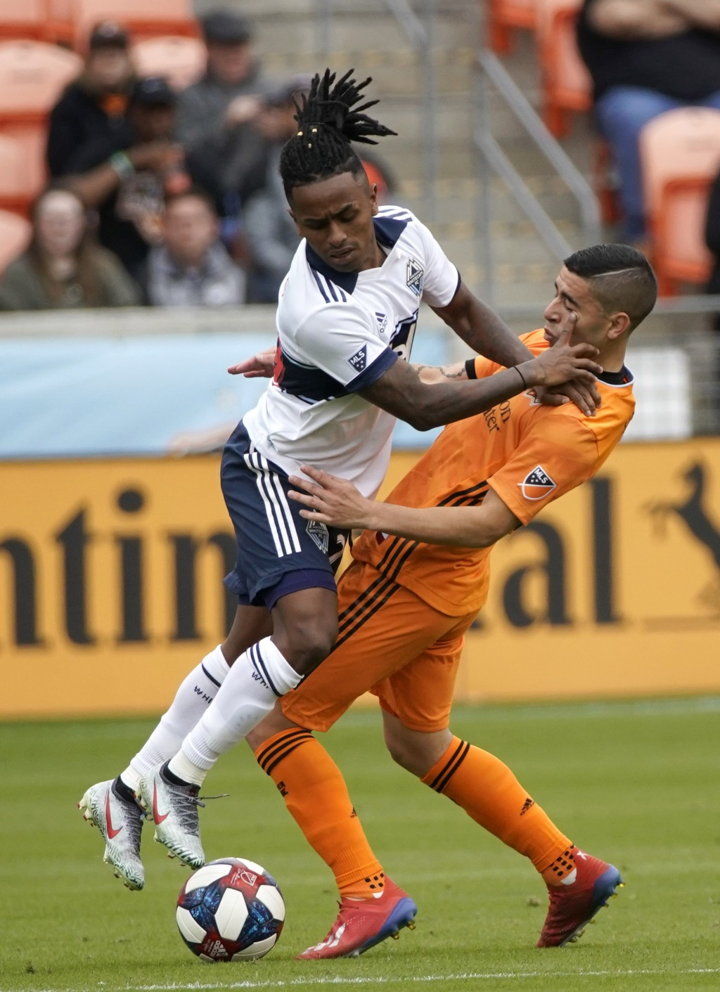 Vancouver Whitecaps's Yordi Reyna, left, collides the Houston Dynamo's Matias Vera during the first half of an MLS soccer match Saturday, March 16, 20