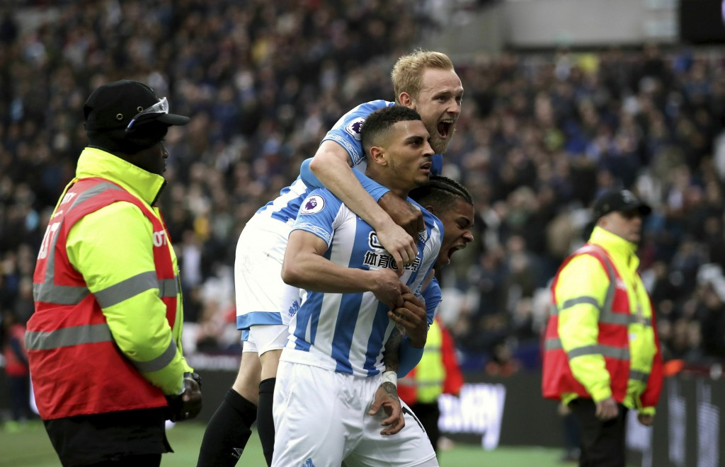 Huddersfield Town's Karlan Grant celebrates scoring his side's third goal of the game with teammates during their English Premier League soccer match