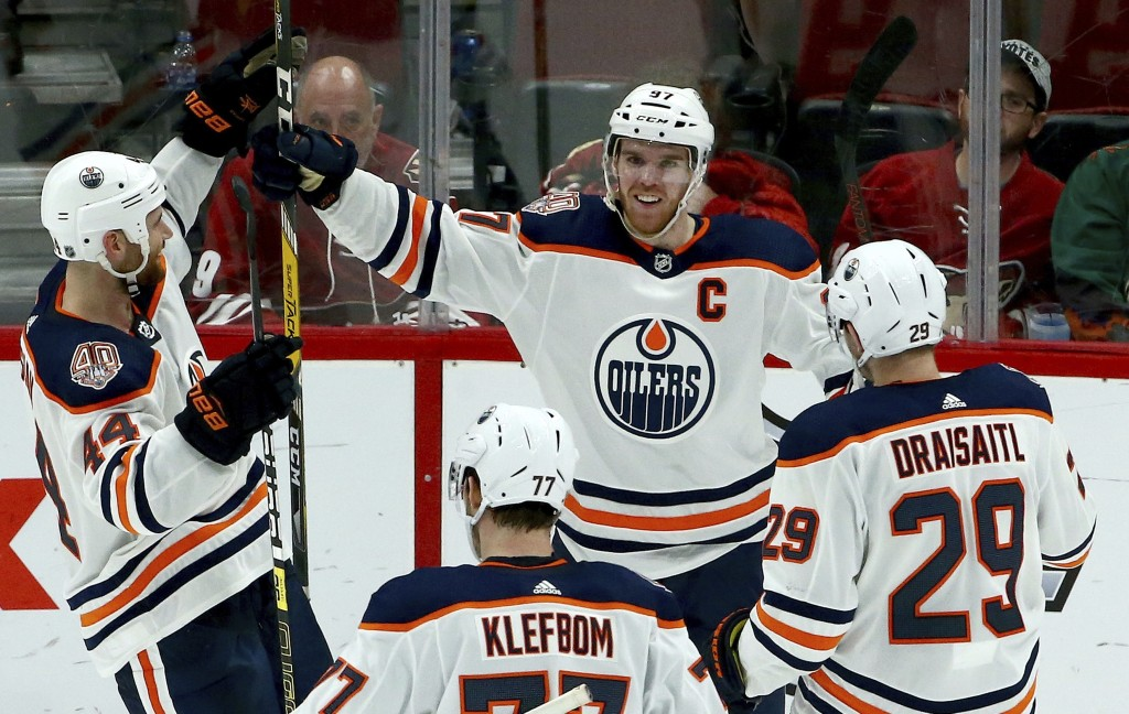 Edmonton Oilers center Connor McDavid (97) smiles as he celebrates his game-winning goal against the Arizona Coyotes with Zack Kassian (44), Oscar Kle
