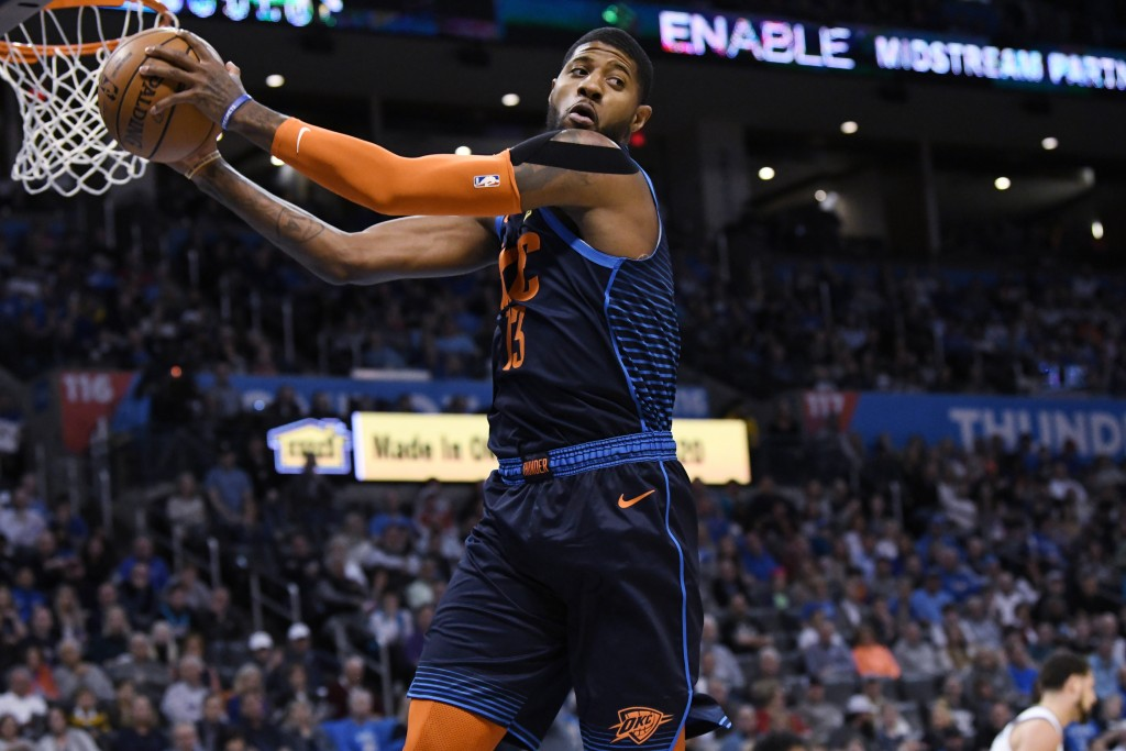 Oklahoma City Thunder forward Paul George (13) grabs a rebound during the first half of the team's NBA basketball game against the Golden State Warrio
