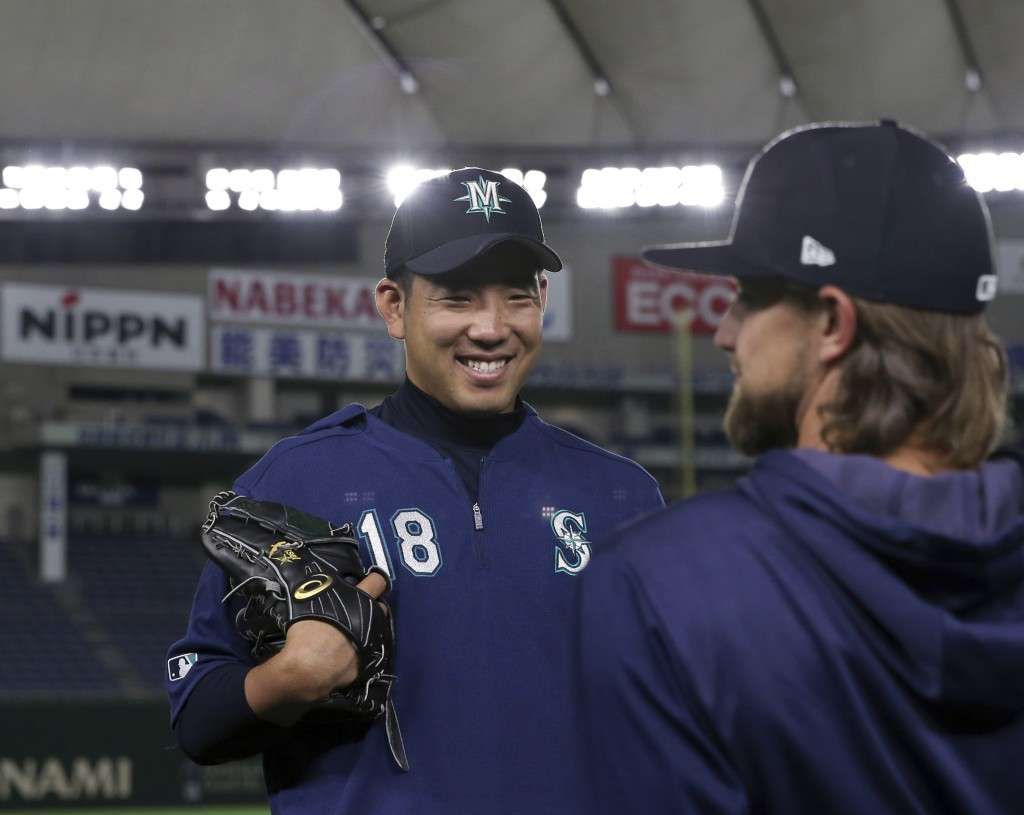 Seattle Mariners pitcher Yusei Kikuchi smiles with his teammate during his team's practice at Tokyo Dome in Tokyo, Saturday, March 16, 2019. Just as h