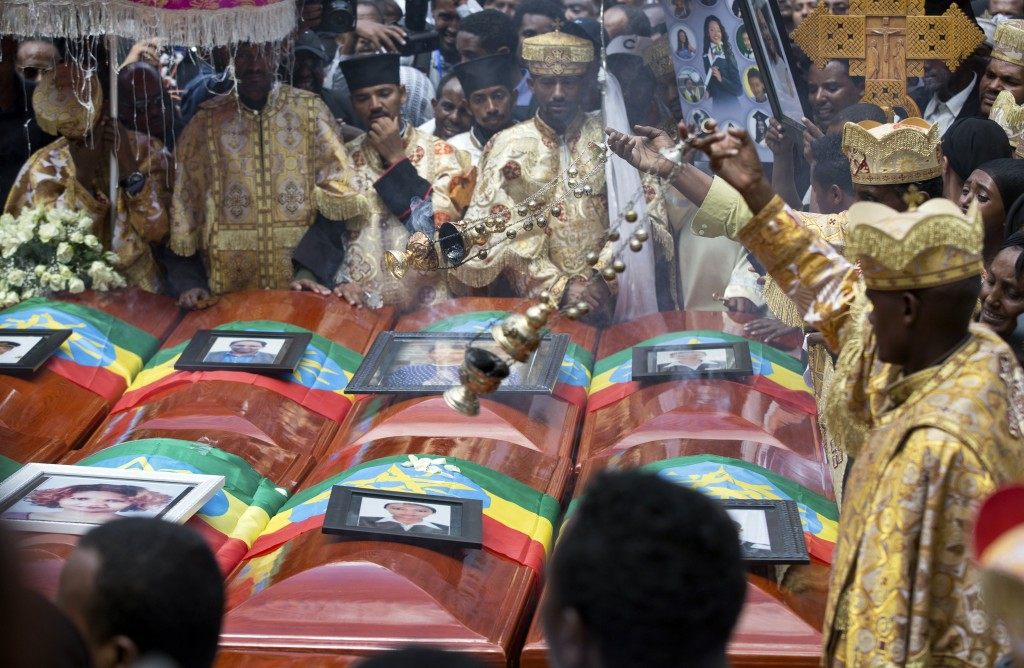 Priests swing incense over empty caskets draped with the national flag at a mass funeral at the Holy Trinity Cathedral in Addis Ababa, Ethiopia Sunday