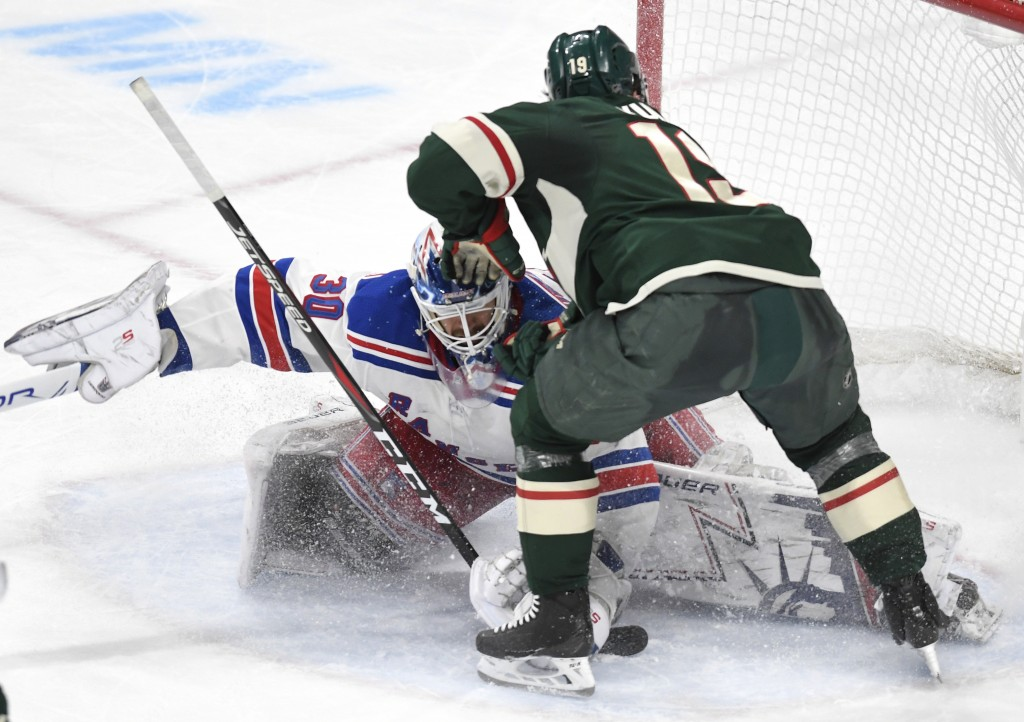 Minnesota Wild's Luke Kunin, right, loses his stick as he attempts to get off a shot against New York Rangers goalie Henrik Lundqvist, left, of Sweden...