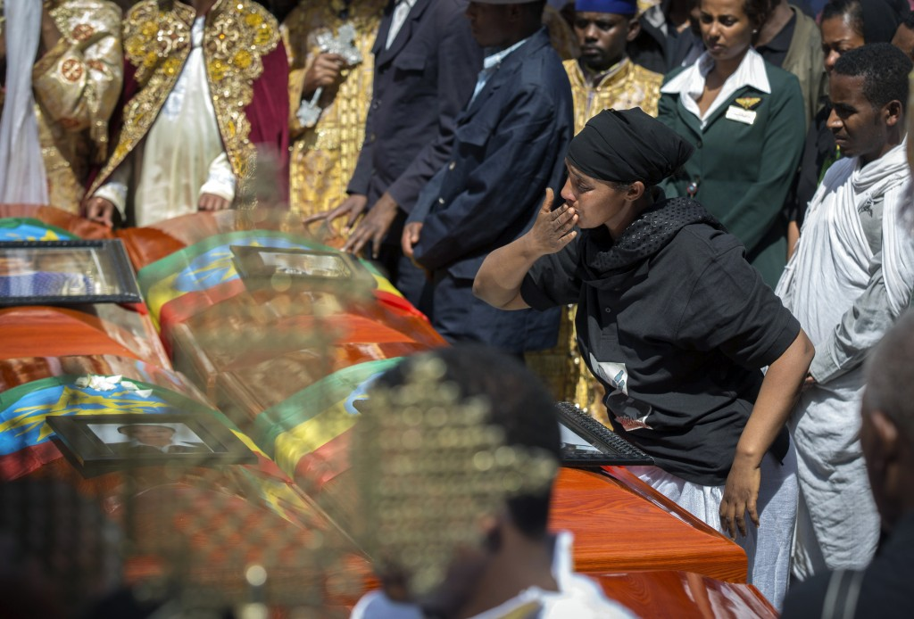 A relative blows a kiss towards empty caskets draped with the national flag at a mass funeral at the Holy Trinity Cathedral in Addis Ababa, Ethiopia S