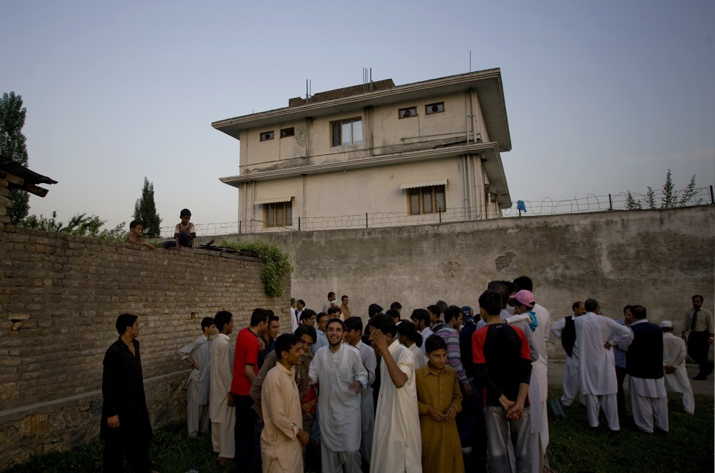 FILE - In this May 3, 2011 file photo, local residents gather outside a house where al-Qaida leader Osama bin Laden was killed in Abbottabad, Pakistan
