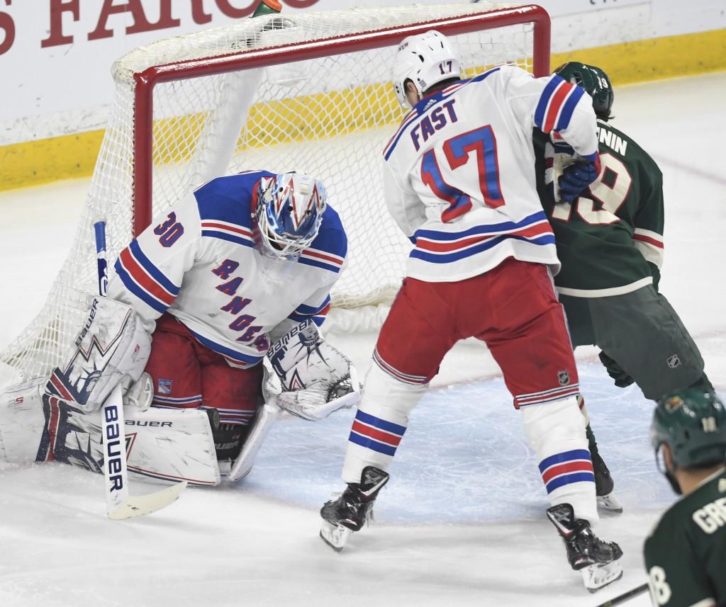 New York Rangers goalie Henrik Lundqvist, left, of Sweden, stops the shot of Minnesota Wild's Luke Kunin, right, as the Rangers' Jesper Fast (17), of ...