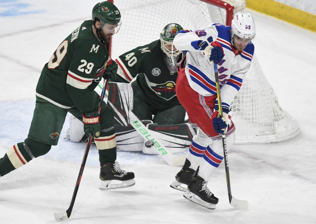 New York Rangers' Pavel Buchnevich, right, of Russia, attempts to tip the puck past Minnesota Wild goalie Devan Dubnyk, center, as the Wild's Greg Pat...