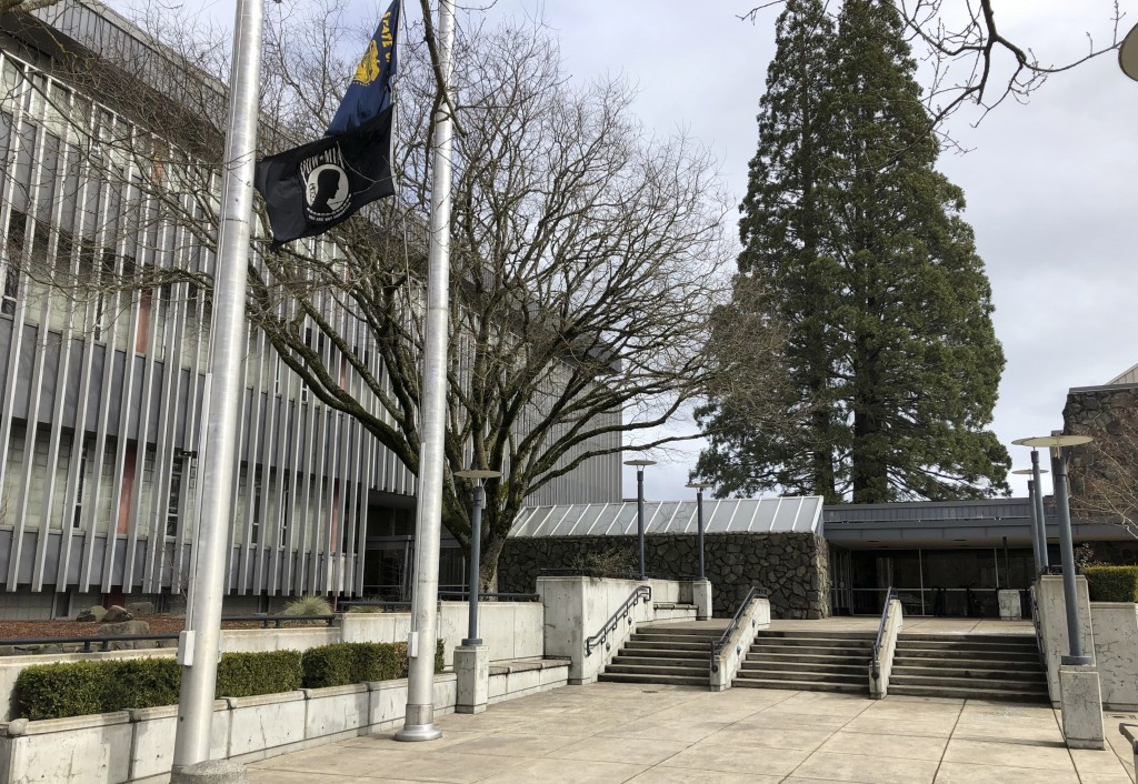 In this photo taken March 7, 2019, flags, including a POW/MIA flag, flap in a breeze in front of the Lane County Circuit Court building where the Vete