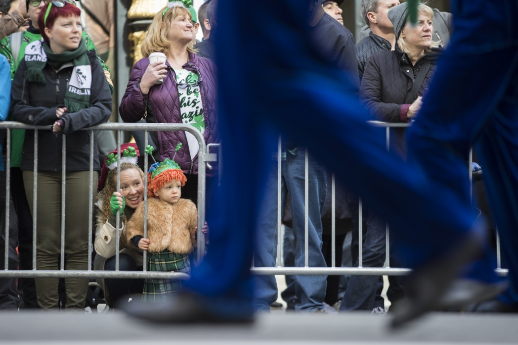 Jennifer McCaffrey, bottom left, and daughter Anastasia, 2, watch the participants march up Fifth Avenue during the St. Patrick's Day Parade, Saturday