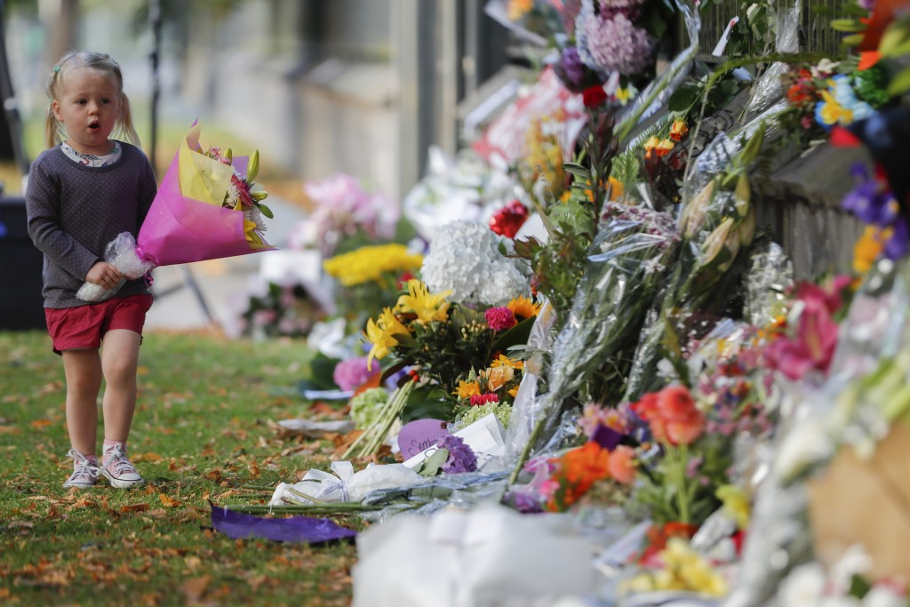 A girl walk to lay flowers on a wall at the Botanical Gardens in Christchurch, New Zealand, Sunday, March 17, 2019. New Zealand's stricken residents r