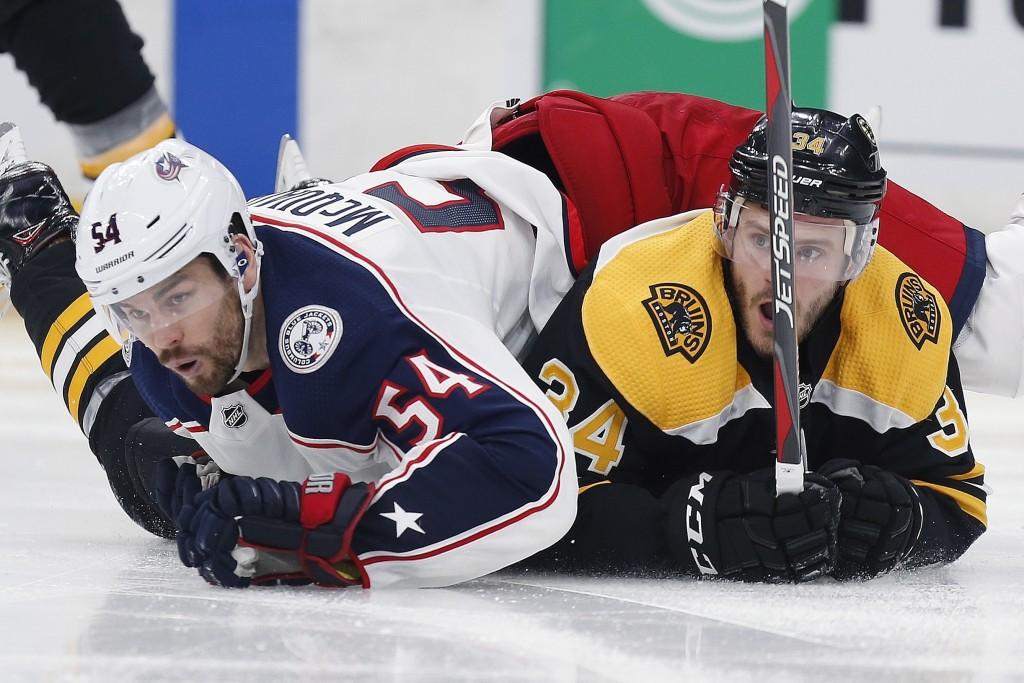 Columbus Blue Jackets' Adam McQuaid (54) falls onto Boston Bruins' Paul Carey (34) during the second period of an NHL hockey game in Boston, Saturday,