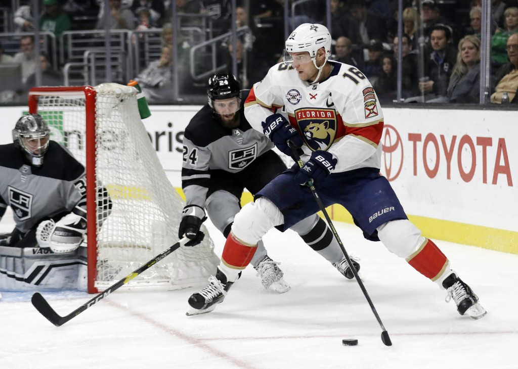 Florida Panthers' Aleksander Barkov (16) is defended by Los Angeles Kings' Derek Forbort, center, during the first period of an NHL hockey game Saturd