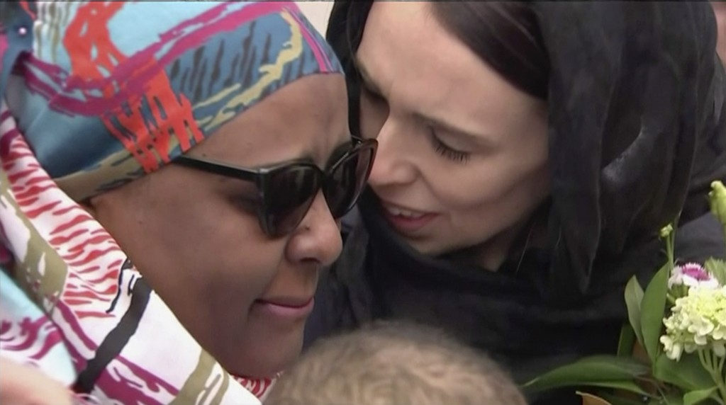 In this image made from video, New Zealand's Prime Minister Jacinda Ardern, right, hugs and consoles a woman as she visited Kilbirnie Mosque to lay fl