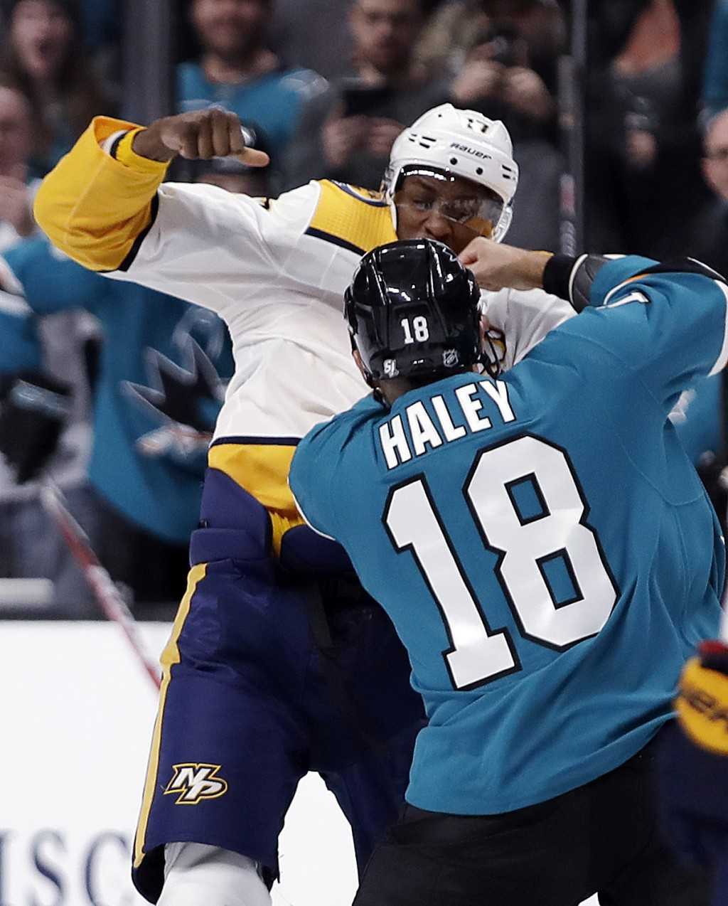 Nashville Predators' Wayne Simmonds, left, and San Jose Sharks' Micheal Haley (18) fight during the first period of an NHL hockey game Saturday, March