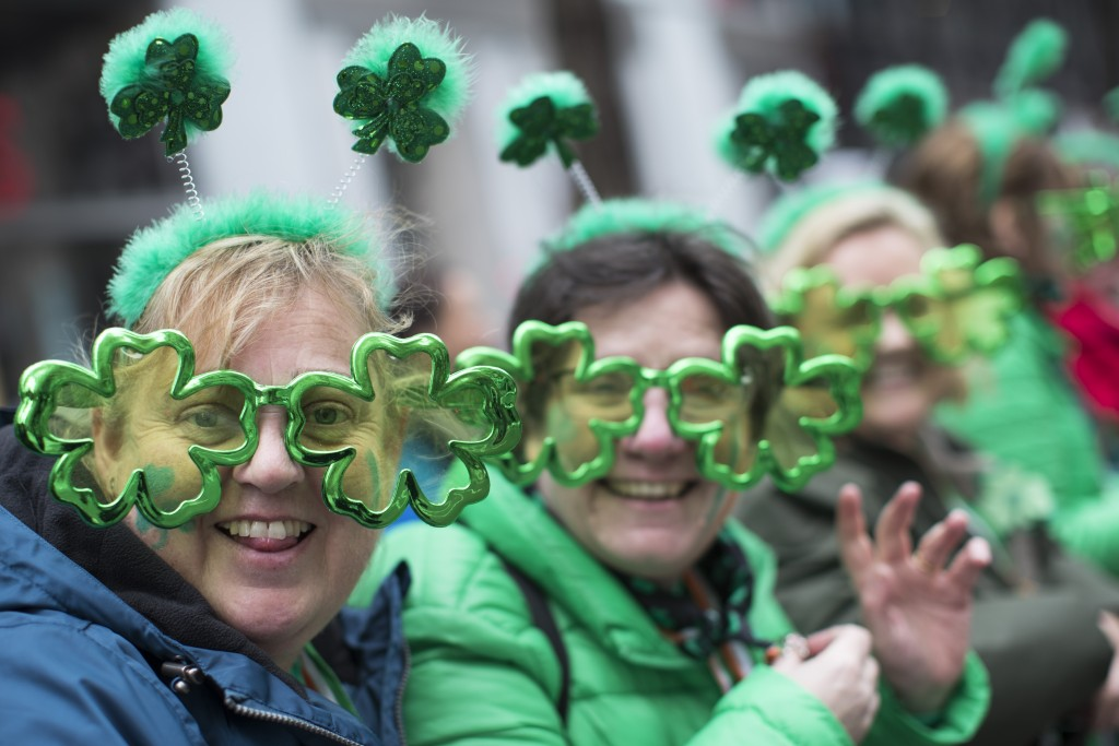 Sharon Keely, left, of Dublin, watches as participants march up Fifth Avenue during the St. Patrick's Day Parade, Saturday, March 16, 2019, in New Yor