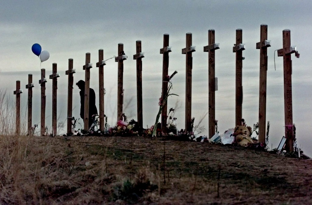 FILE - In this April 28, 1999, file photo, a woman stands among 15 crosses posted on a hill above Columbine High School in Littleton, Colo., in rememb
