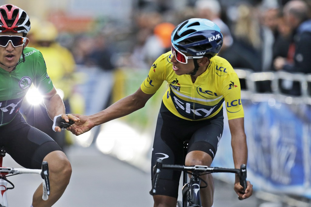 Colombia's Egan Arley Bernal Gomez, wearing the overall leader's yellow jersey, thanks teammate Poland's Michal Kwiatkowski, wearing the best sprinter