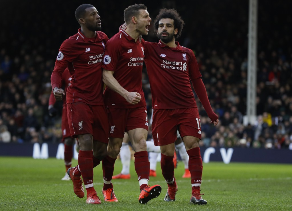 Liverpool's James Milner, center, celebrates after scoring his side's second goal, during the English Premier League soccer match between Fulham and L