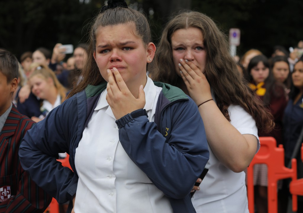 In this Monday, March 18, 2019, file photo, students react as they gather for a vigil to commemorate victims of Friday's shooting, outside the Al Noor...
