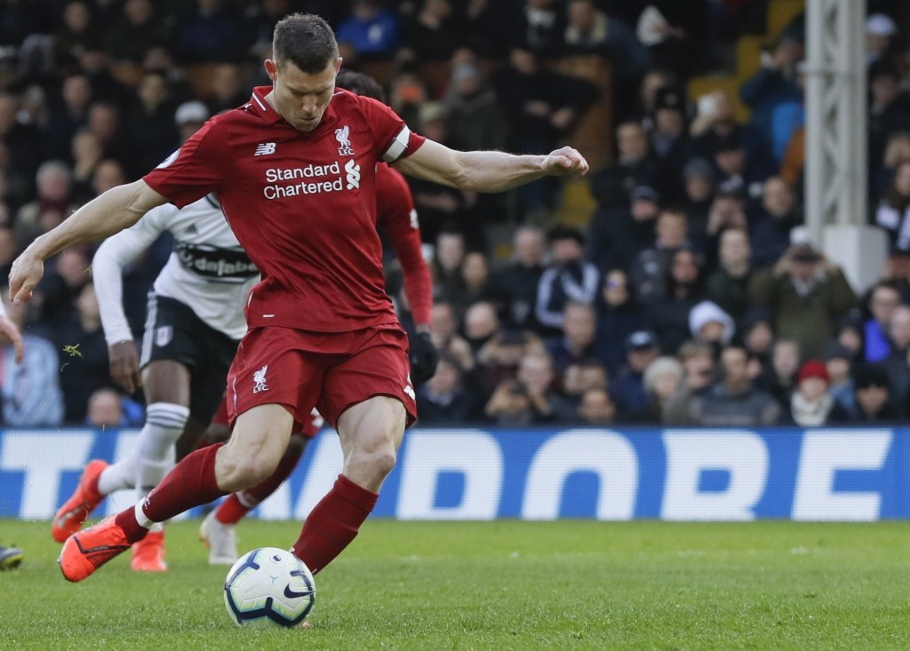 Liverpool's James Milner scores his side's second goal on a penalty kick, during the English Premier League soccer match between Fulham and Liverpool