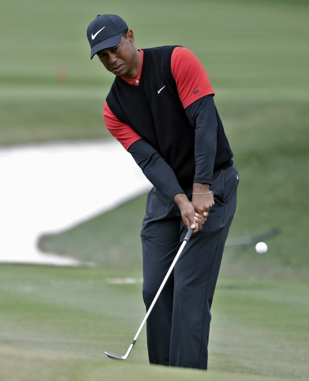 Tiger Woods chips onto the ninth green during the final round of The Players Championship golf tournament Sunday, March 17, 2019, in Ponte Vedra Beach...