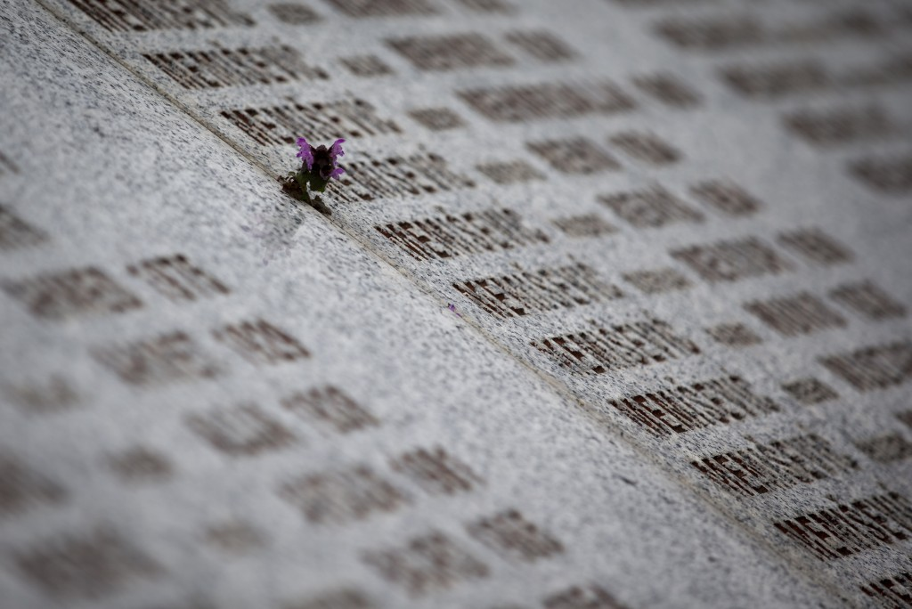 In this Saturday, March 16, 2019 photo, a flower is placed next to a name of a massacre victim carved in memorial cemetery in Potocari, near Srebrenic...