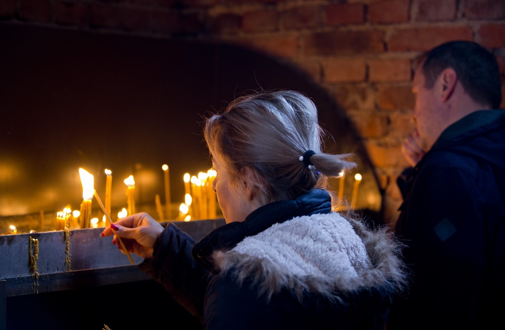 In this Sunday, March 17, 2019 photo, a woman lights a candle at an Orthodox church in the Bosnian Serb wartime stronghold of Pale, Bosnia-Herzegovina