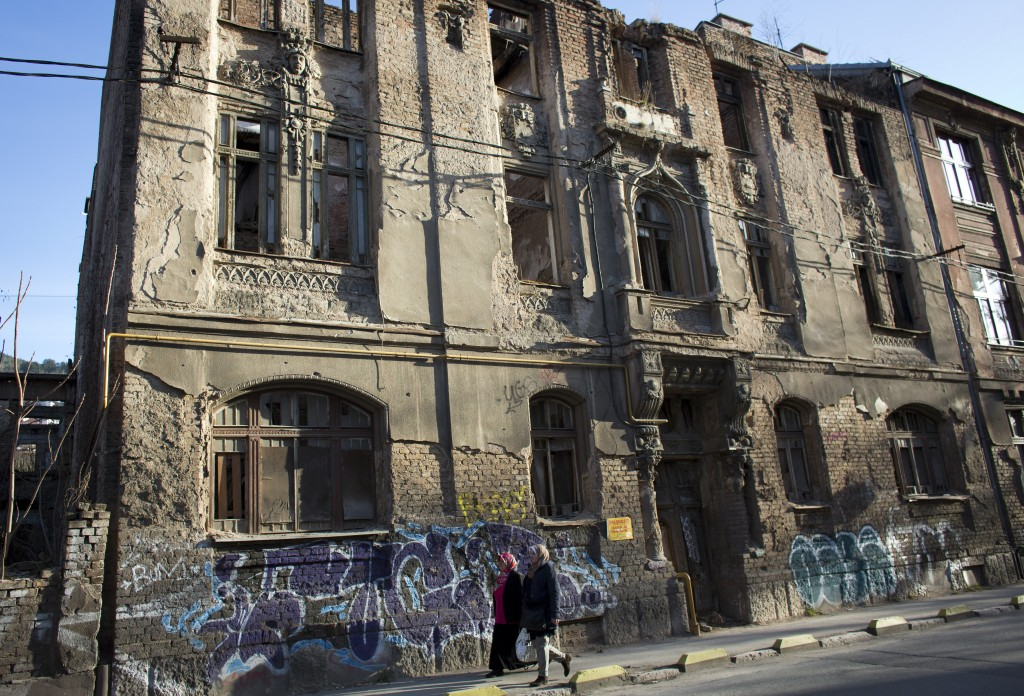 In this Sunday, March 17, 2019 photo, women walk past a war damaged building in Sarajevo, Bosnia-Herzegovina. Nearly a quarter of a century since Bosn...