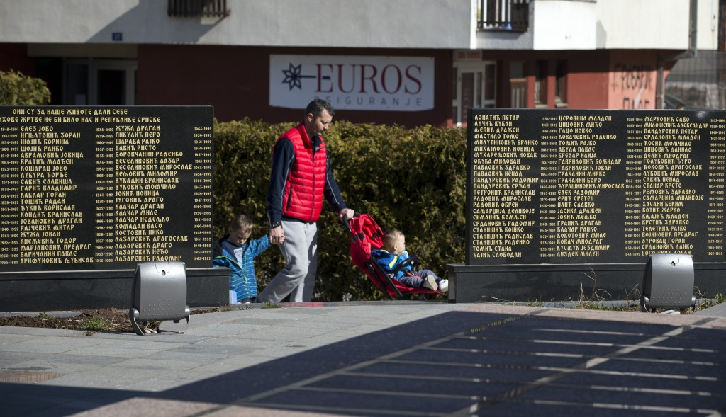 In this Sunday, March 17, 2019 photo, a man walks his children past the monument for Bosnian Serbs killed in 1990s war in the Bosnian Serb wartime str