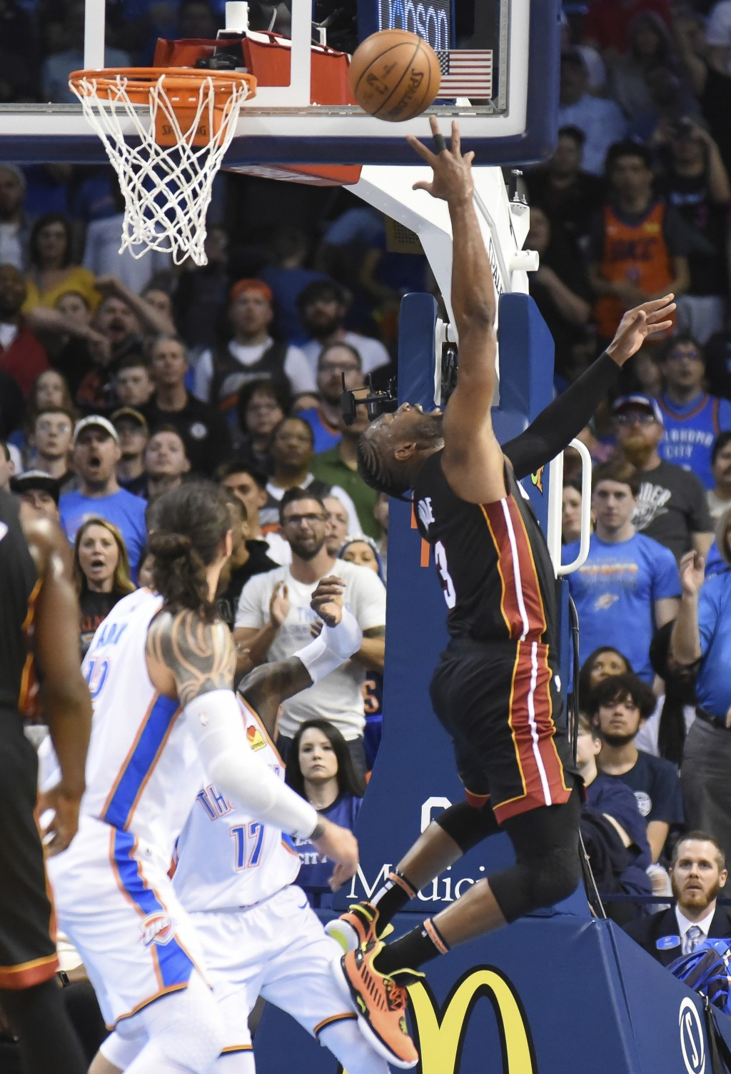 Miami Heat guard Dwyane Wade (3) shoots over Oklahoma City Thunder center Steven Adams in the second half of an NBA basketball game Monday, March 18, ...