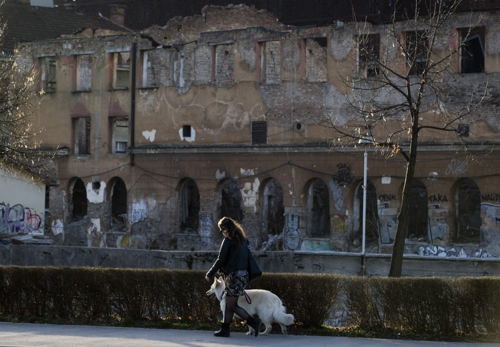 In this Sunday, March 17, 2019 photo, a woman walks a dog past a war damaged building in Sarajevo, Bosnia-Herzegovina. Nearly a quarter of a century s