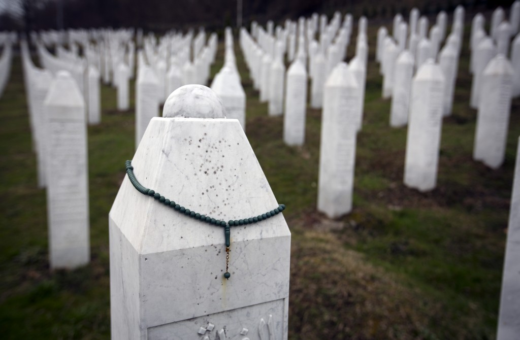 In this Saturday, March 16, 2019 photo, a chaplet hangs on a tomb at the memorial cemetery for massacre victims in Potocari, near Srebrenica, Bosnia-H